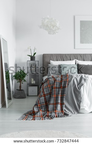 Cozy interior of a monochromatic bedroom with a king-size bed and checkered bedclothes lying on it #732847444