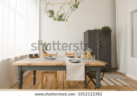 Cozy interior of kitchen with wooden table and cupboard and green plants in decor.  #1052122382