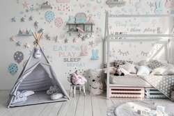 Cozy kids bedroom and playroom with toys, house decor, teepee tent, plaid at comfort bed and decorated wall in contemporary interior. Apartment with nursery room for childs