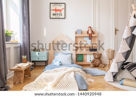 Cozy kids bedroom with blue bedding and warm blanket on the bed, real photo with mockup poster on the floor