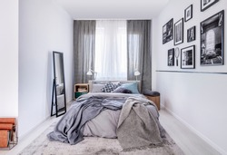Cozy king size bed with grey bedding and warm blanket in elegant bedroom interior with mirror and photos on the wall