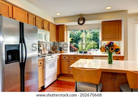 Cozy kitchen with honey color cabinets, white appliances and kitchen island with fresh flowers
