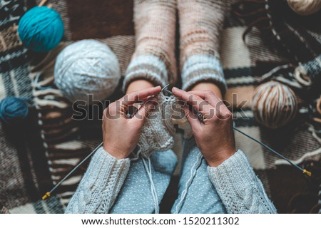 Cozy knitting woman in knitted winter warm socks and in pajamas enjoys knit work on brown checkered plaid blanket at home in cozy winter time. Top view