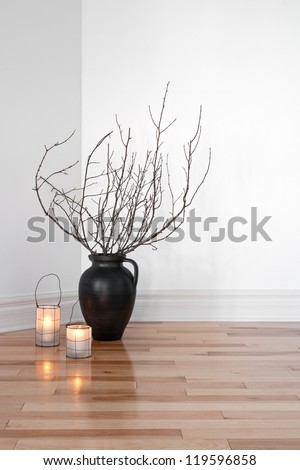 Cozy lanterns and tree branches in a vase, decorating a room.