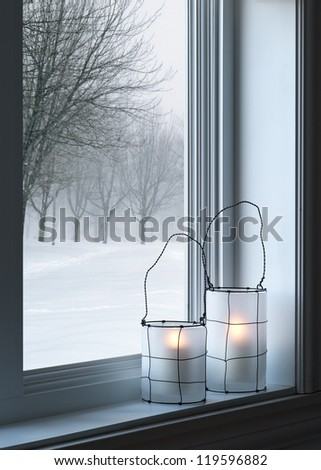 Cozy lanterns on a windowsill, with winter landscape seen through the window.