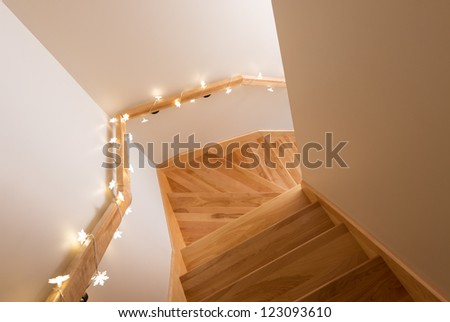 Cozy lights decorating wooden staircase. Home interior.