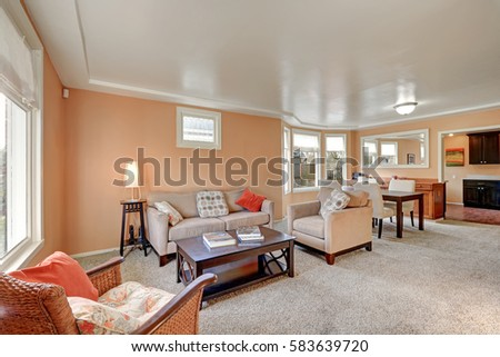 Cozy living room interior with peach walls, beige sofa with bright pillows, wood stained cocktail table and wicker chair with colorful cushion. Northwest, USA #583639720