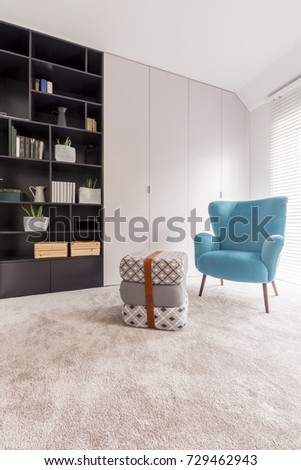 Cozy looking blue chair standing next to three cushions strapped with a leather belt in the middle of a monochromatic day room #729462943