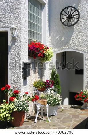 Cozy mediterranean garden with geranium flower pots