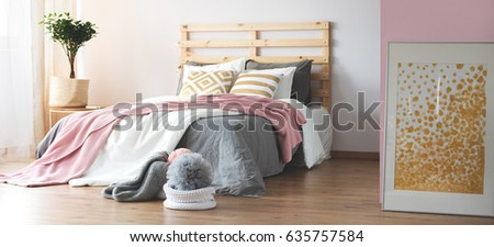 Cozy modern bedroom with wooden floor and grey and pink decor #635757584