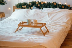 Cozy New Year's composition, two mugs with hot drinks on a wooden tray stand on the bed against the background of a festive Christmas tree in the interior of a loft room decorated with garlands