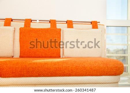 Cozy orange and white sofa with pillows