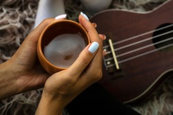 Cozy photo of woman's hands holding cup of tea with ukulele on backdrop. Fall or winter time concept. Wellbeing and simple pleasures concept