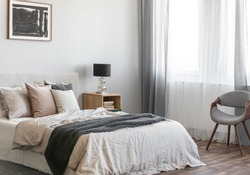 Cozy pillows on comfortable big king size bed in bright bedroom interior in elegant apartment
