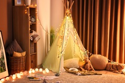 Cozy play tent for kids with glowing garland in room interior