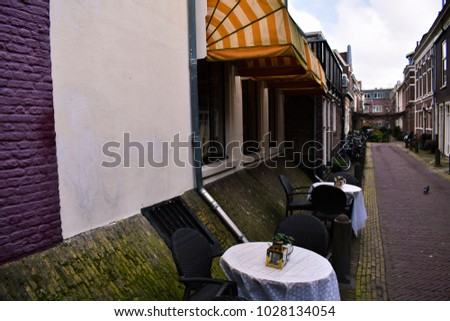 Cozy Restaurant In Amsterdam Yellow White Awning Red Purple Wall Mossy Bricks Cozy Terrace Soft Bench Colorful Pillows Green Yellow Blue Pink Grey Chair Table #1028134054