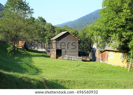 Cozy rural patio in a mountainous region. Old wooden shed for storing hay.