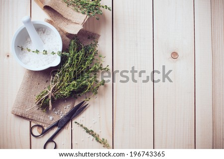 Cozy rustic home kitchen still life, dried herbs thyme, salt in white mortar, old wooden box and vintage scissors on a table background.