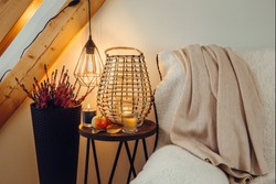 Cozy sheepskin sherpa textile cover blanket on sofa, small side table with wood lantern candle burning, black metal wire spiral led bulb illuminated. Autumn hygge concept.