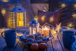 Cozy sitting area with coffee and cookies on a balcony, decorated in winter with lanterns, candles, woolen blankets and fairy lights