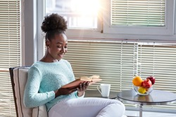 Cozy sofa and a beautiful girl, reading a book, concepts of home and comfort, place for text. Beautiful young black woman reading book near window at home
