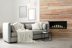 Cozy sofa with pillows and plaid near decorative fireplace in living room. Interior design