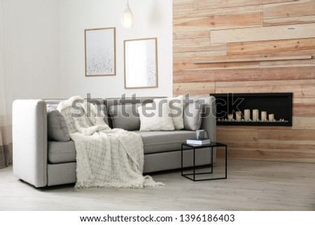 Cozy sofa with pillows and plaid near decorative fireplace in living room. Interior design #1396186403