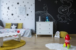 Cozy space-themed children's room with blackboard wall
