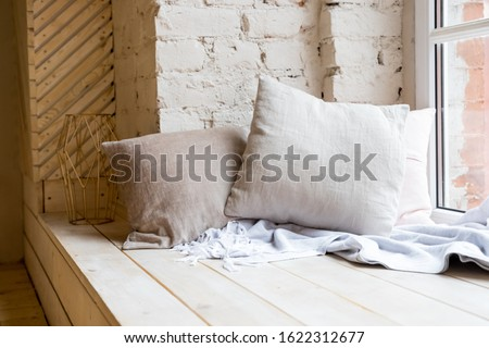 cozy still life, warm woolen knitting decoration on windowsill against brick wall and window.boho style in living room interior with elegant pillows. loft apartment. Home decor on windowsill.