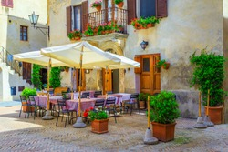Cozy street cafe and restaurant decorated with colorful flowers, Pienza, Tuscany, Italy, Europe