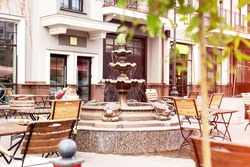 Cozy street cafe with wooden tables, chairs and fountain. Architecture and landmark  cityscape. Outdoor cafe on sunny summer day. Nobody.