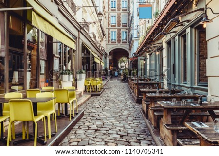 Cozy street near Boulevard San-German with tables of cafe and pub  in Paris, France. Architecture and landmarks of Paris. Postcard of Paris
