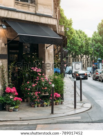 Cozy street with flower shop in Paris, France. Architecture and landmarks of Paris. Postcard of Paris