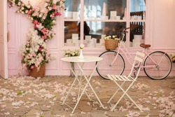 Cozy street with flowers and French-style cafe table. Empty cafe terrace with white table and chair. Pink exterior of the cafe restaurant. interior Street cafe. Decor facade of coffeehouse with bike.