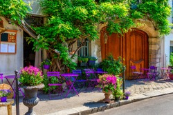 Cozy street with flowers and tables of cafe  in Paris, France. Architecture and landmarks of Paris. Postcard of Paris