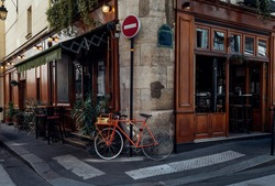 Cozy street with tables of cafe and old bicycle in Paris, France. Architecture and landmarks of Paris. Postcard of Paris