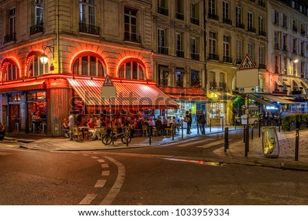 Cozy street with tables of cafe in Paris at night, France. Architecture and landmarks of Paris. Postcard of Paris