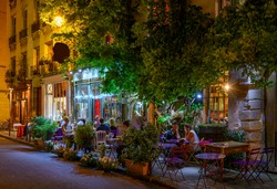 Cozy street with tables of cafe in Paris, France. Night cityscape of Paris. Architecture and landmarks of Paris.
