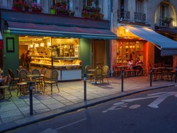 Cozy street with tables of cafe in Paris, France. Night cozy cityscape of Paris. Architecture and landmarks of Paris.