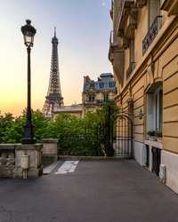 Cozy street with view of Paris Eiffel Tower in Paris, France. Eiffel Tower is one of the most iconic landmarks in Paris. Architecture and landmark of Paris. Eiffel tower in summer, France.