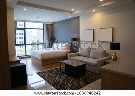 Cozy studio apartment design with bedroom and living space. Hotel room panoramic window, double bed, sofa and coffee table. Urban apartment concept #1086948242