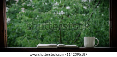 Cozy summer still life: cup of hot coffee and opened book on vintage windowsill and rain outside. Apartment. Rain in the summer.