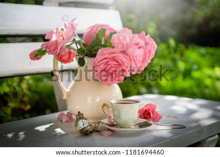 Cozy tea party at garden with book, teapot, candle, flowers, blanket. Beautiful metal lacy chairs and table. Nobody #1181694460