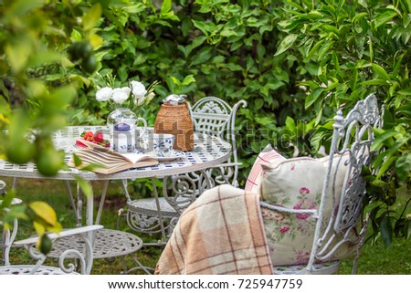 Cozy tea party at garden with book, teapot, candle, flowers, blanket. Beautiful metal lacy chairs and table. Nobody #725947759