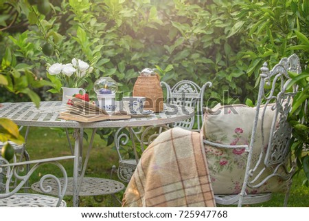 Cozy tea party at garden with book, teapot, candle, flowers, blanket. Beautiful metal lacy chairs and table. cosiness. tranquility. relaxation. Sunlight. Nobody #725947768