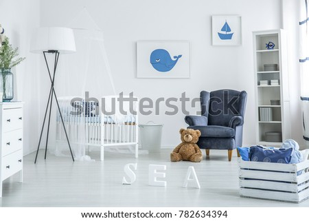 Cozy white and blue nursery with suede armchair and whale poster over a wooden crib