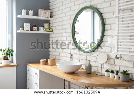 Cozy white bathroom with brick wall and wooden counter. Scandinavian interior of bathroom with wooden counter, round mirror and plants in industrial style.