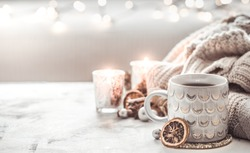 cozy winter composition with a cup and sweater on a light festive background