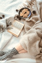Cozy winter day at home in bed with warm knitted blanket, book and gingerbread. Woman wearing warm woolen socks on cold winter weekend. Christmas, relaxation and hygge concept