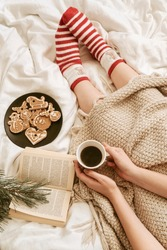 Cozy winter day at home in bed with warm knitted blanket, book, coffee and gingerbread. Woman wearing warm woolen socks on cold winter weekend. Christmas, relaxation and hygge concept